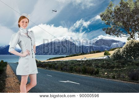 Pretty air hostess with hand on hip against scenic backdrop