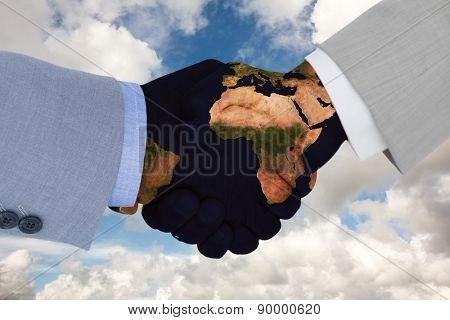 Close up side view of shaking hands against blue sky with white clouds
