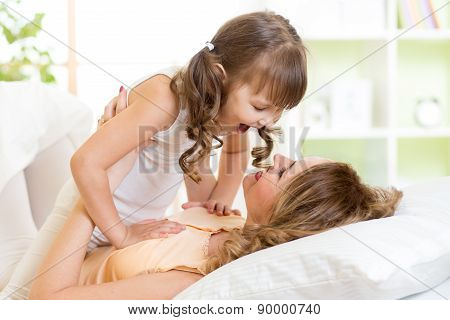 Happy mom playing with her kid in bed enjoying  sunny morning in home bedroom