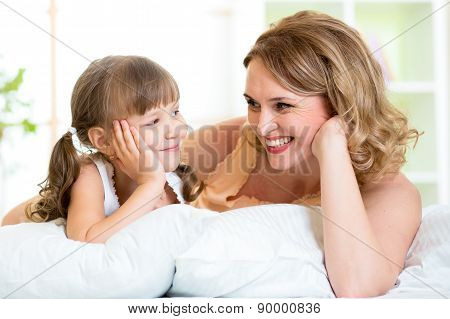 happy mom and daughter lie on bed and look each at other
