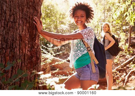 Women Pausing By Tree Trunk In On Walk Through Forest