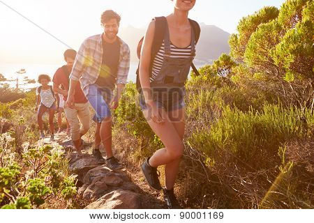 Group Of Friends Walking Along Coastal Path Together