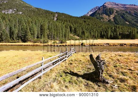 Alpine Valley in Austria. Scenic farm fields blocked by the wooden fence. Steep mountain slopes overgrown with coniferous forests
