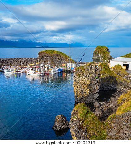 White fishing boat in the harbor pier village Arnastapi. Sunset on the sea fjord in Iceland