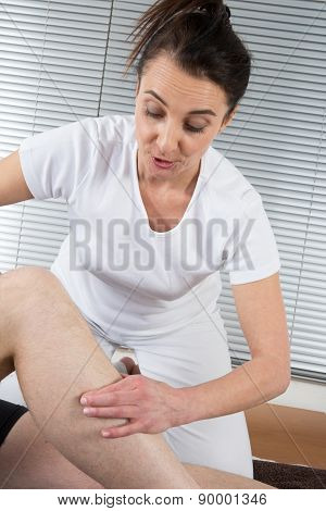 Portrait Of Female Therapist Doing Leg Massage