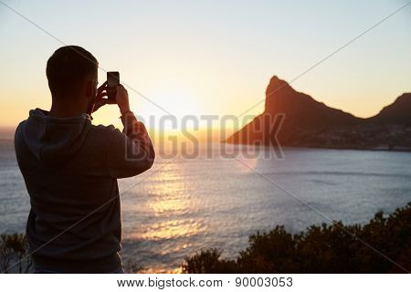 Man Taking Picture Of Sun Setting Over Sea On Mobile Phone