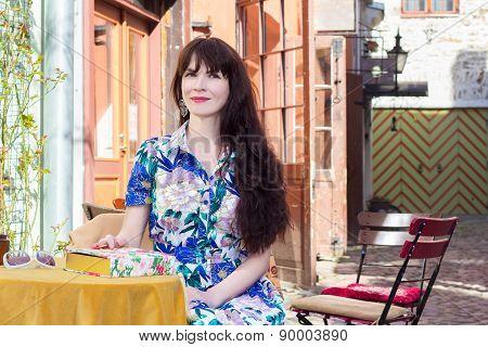 Portrait Of Beautiful Woman In Dress Sitting In Street Cafe