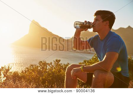 Young man drinking after jogging