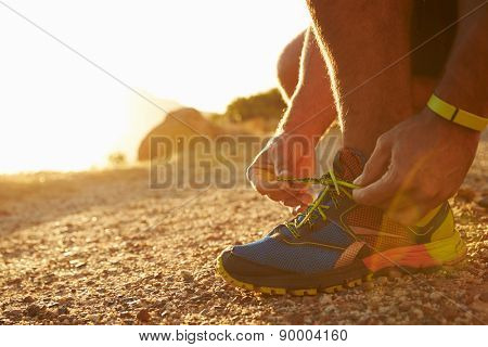 Close up of a man doing up his running shoes