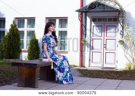 Beautiful Woman In Dress Sitting On The Bench In Old Town Of Tallinn, Estonia
