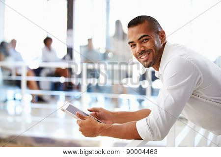 Portrait of man in office using tablet