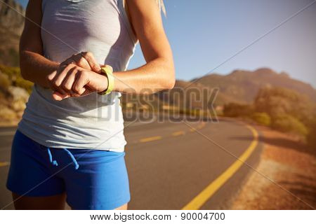 Cropped shot of woman checking her sports watch