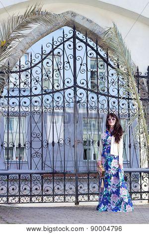Beautiful Woman In Long Dress Posing Over Old Metal Gates In Old Town Of Tallinn