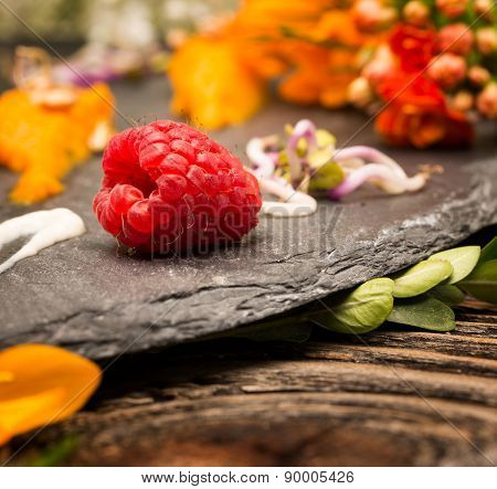 Selective focus on the tempting raspberry lying near the edge of a fancy plate