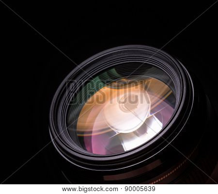 Photo lens closeup with colorful reflections. Black background