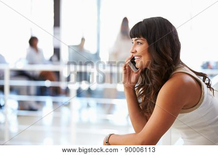 Portrait of smiling woman in office with smart phone