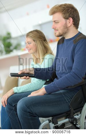 Disabled man watching TV with his girlfriend