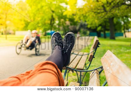 The Legs Of A Woman Lying On A Bench