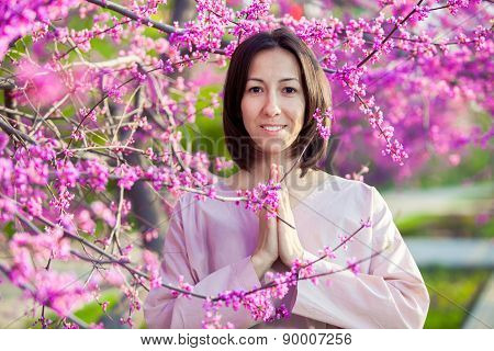 woman doing yoga on the background of a blooming garden, oriental cherry.