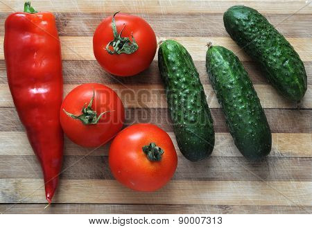 Tomato, Cucumber And Red Pepper On A Wooden Table