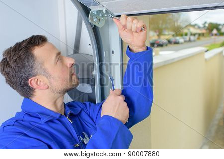 Man installing a garage door poster