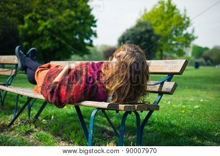 Woman Lying On A Bench In The Park