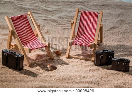 kkleine deck chairs on the sandy beach with suitcases