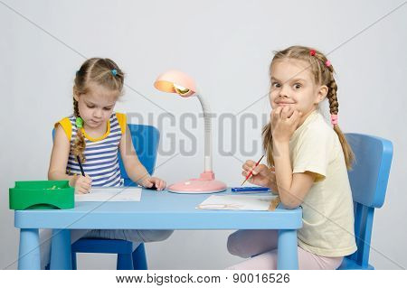 Two Sisters Draw Sitting At The Table