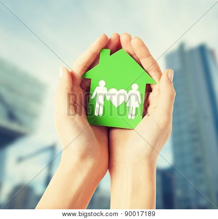 real estate and family home concept - closeup picture of female hands holding green paper house with family