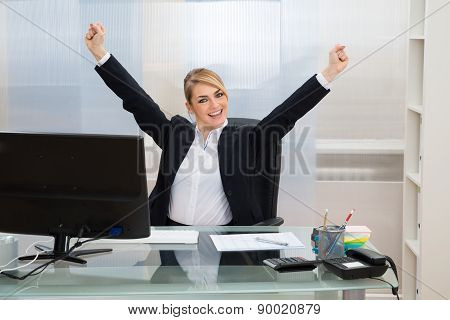Businesswoman Raising Hands In Office