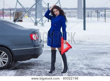 Attractive woman with a warning triangle in the hands of waiting for help near her car