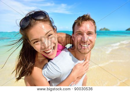 Happy beach couple in love on summer vacations on Lanikai beach, Oahu, Hawaii, USA with Mokulua Islands. Joyful Asian girl piggybacking on young Caucasian boyfriend and having fun on travel holiday.