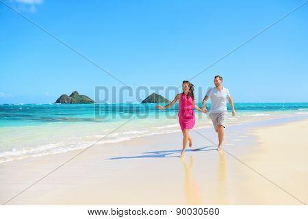 Beach happy couple on running having fun on Hawaii. Romantic couple joyful and full of happiness on travel vacation on Lanikai beach, Oahu, Hawaii, USA with Mokulua Islands. Asian woman, Caucasian man poster