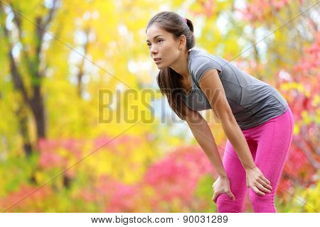Athlete runner resting after running - Asian woman. and jogging training outdoors in forest. Tired exhausted beautiful sports fitness model living healthy active lifestyle. Mixed race Asian Caucasian.