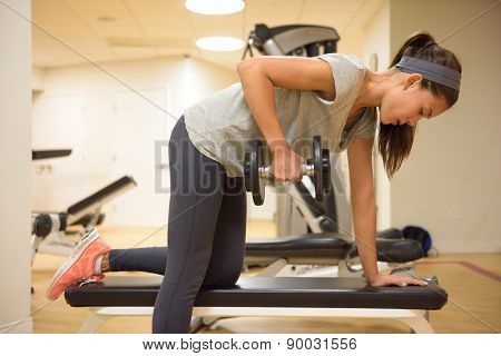 Fitness gym woman strength training lifting dumbbell weights in Bent-over One-Arm Dumbbell Row. Female fitness girl exercising indoor in fitness center. Beautiful fit mixed race Asian Caucasian model.