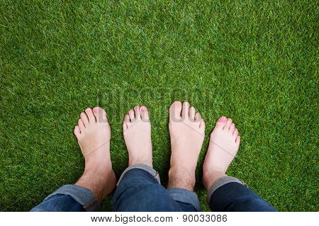 Couple mixed legs standing together on grass