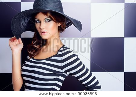 Attractive fashion model posing in dress in black and white stripes on a background of black and white squares. Beauty, fashion concept.
