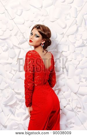 Seductive sensual woman in elegant red suit on a background of white flowers. Beauty, fashion.