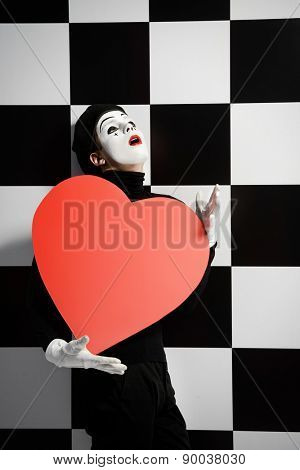 Portrait of a male mime artist holds large red heart expressing love. Chess board background.
