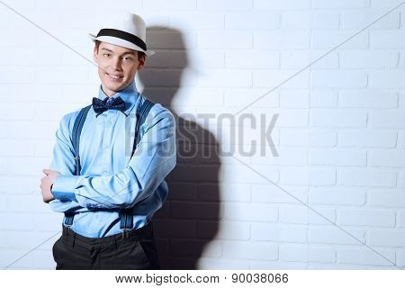 Romantic young man stands by the brick wall and smiling to camera. Men's beauty, fashion.