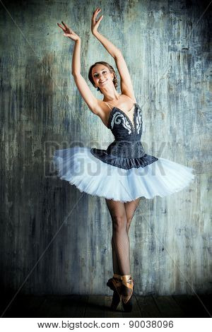 Professional ballet dancer posing at studio over grunge background. Art concept.
