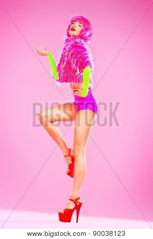Fashionable young woman alluring in sexy vivid colourful clothes and high heels platform shoes. Bright fashion. Pin-up, pink style. Full length portrait.