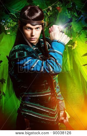 Beautiful warrior elf with a dagger in his hand in the magic forest. Fantasy. Fairy tale, magic.