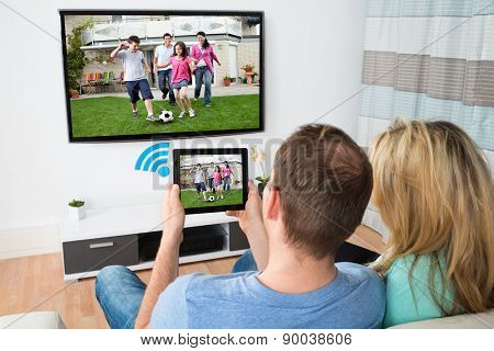 Couple Connecting Television And Digital Table With Wifi