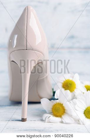 Female shoe with flowers on wooden background