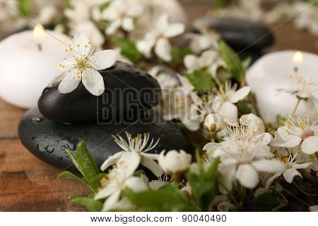 Spa stones with candles and spring flowers on table close up