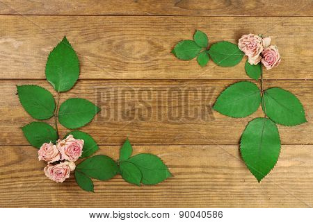 Beautiful dry flowers and leaves on wooden background