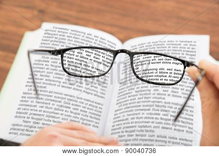 Person Hand Holding Glasses With Book