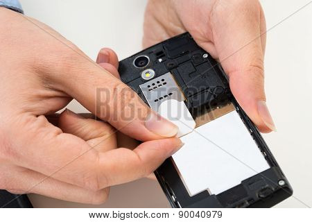 Person Hand With Sim Card And Mobile Phone