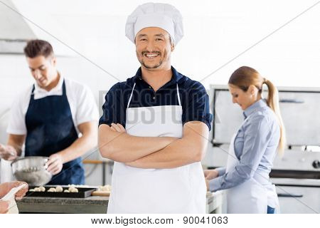 Portrait of confident male chef standing arms crossed while colleagues working in background at commercial kitchen